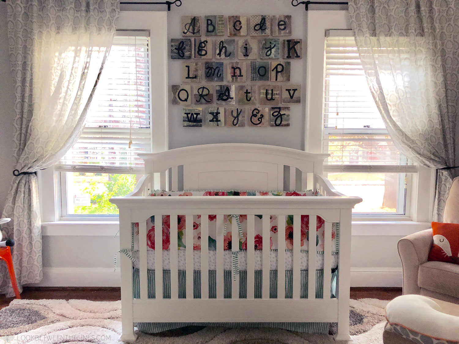 Baby girl's crib with a floral pattern bumper, bright windows, and the ABC's hanging on the wall.
