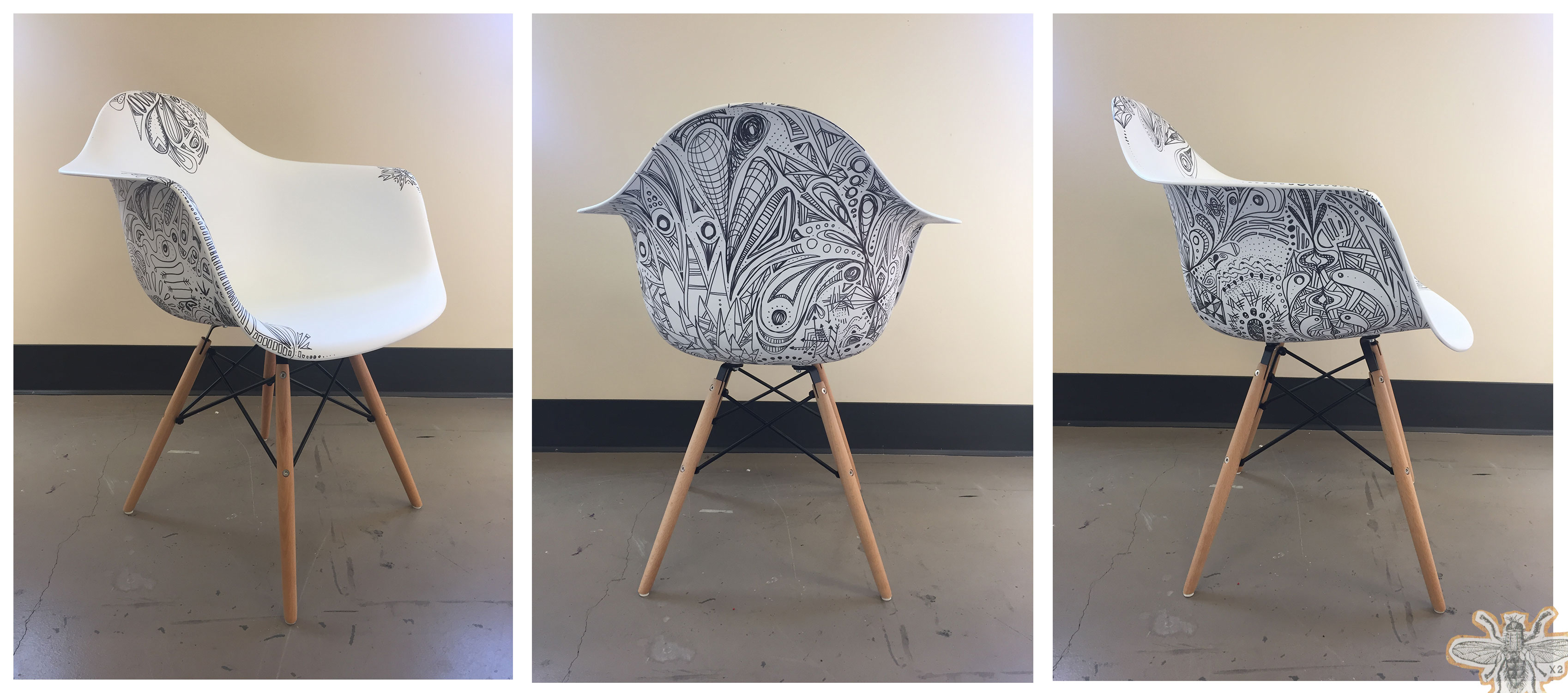 A modern white chair that has been decorated with Sharpie doodles.